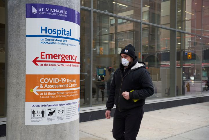 A man wearing a protective face mask walks past St. Michael's Hospital in Toronto on Jan. 11, 2021, amid the ongoing COVID-19 pandemic.