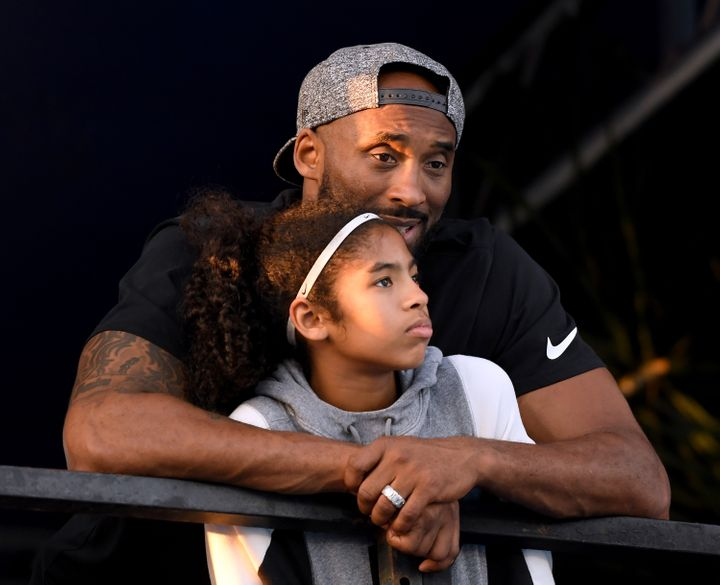 Kobe Bryant and daughter Gianna Bryant watch during day 2 of the Phillips 66 National Swimming Championships at the Woollett