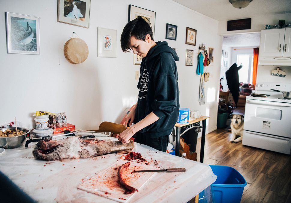 Iris's son Tanner cuts up caribou meat at his grandmother's