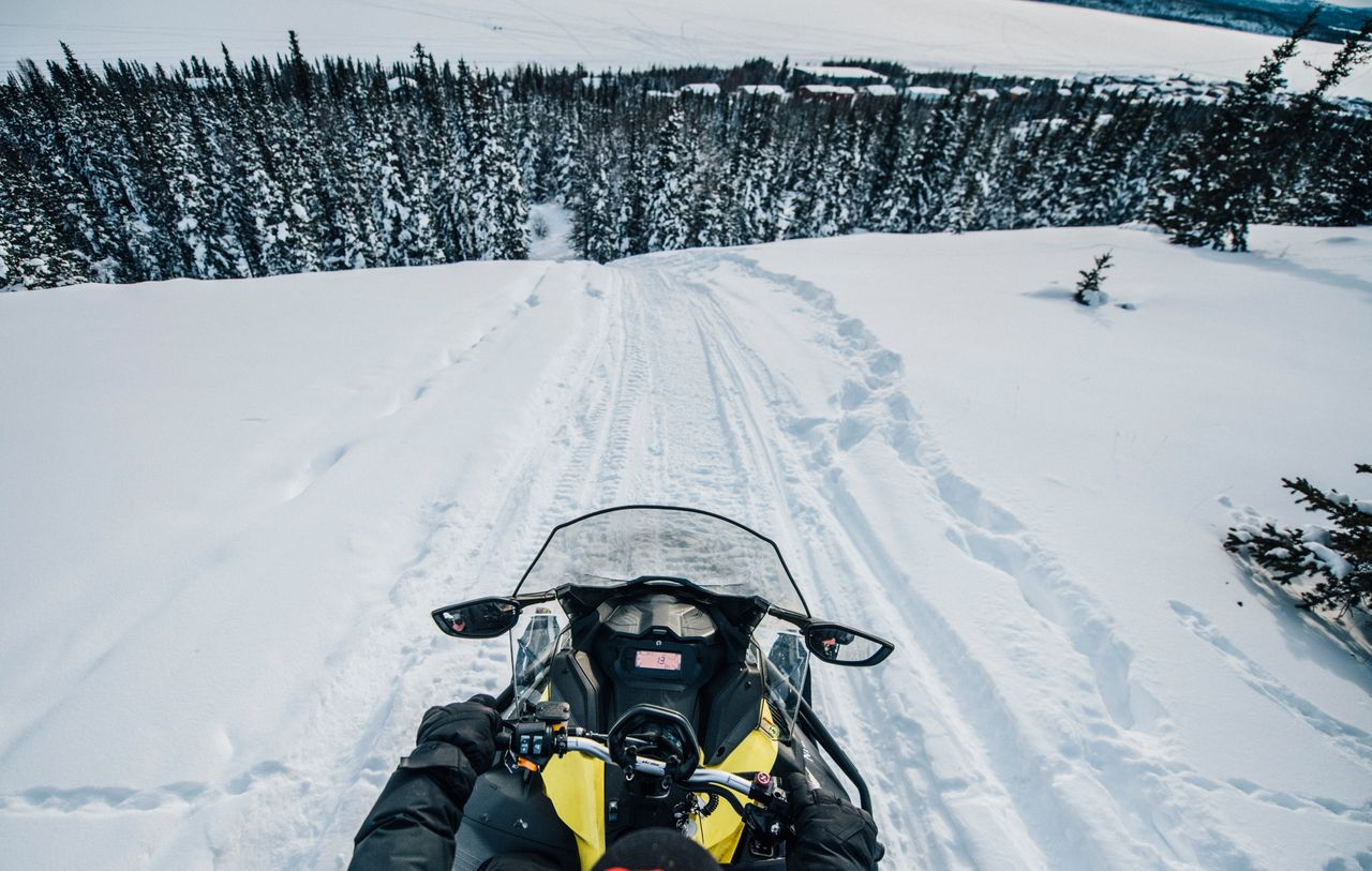 Going down a large hill on the back of a snowmobile in the Thaidene Nëné Indigenous Protected Area.