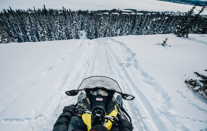 Going down a large hill on the back of a snowmobile in theThaidene Nëné Indigenous Protected Area.