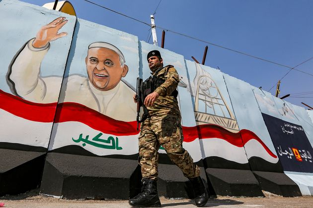 A member of the Iraqi forces walks past a mural depicting Pope Francis waving next to an Iraqi national...