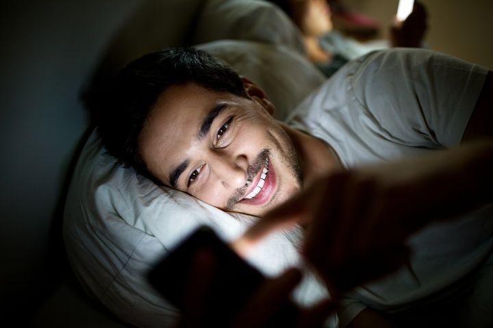 Un joven mira el móvil en la cama.