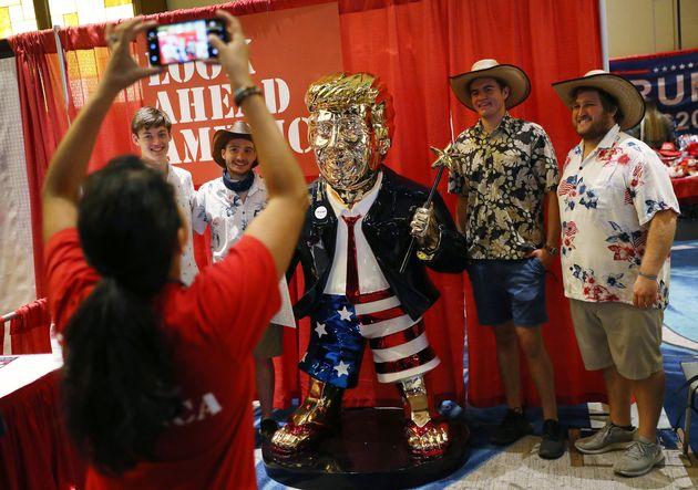 Plusieurs personnes posent avec une statue de l'ancien président américain Donald Trumpà la