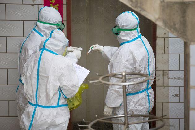 Des soignants en tenues de protection collectent des échantillons lors de tests de recherche de...
