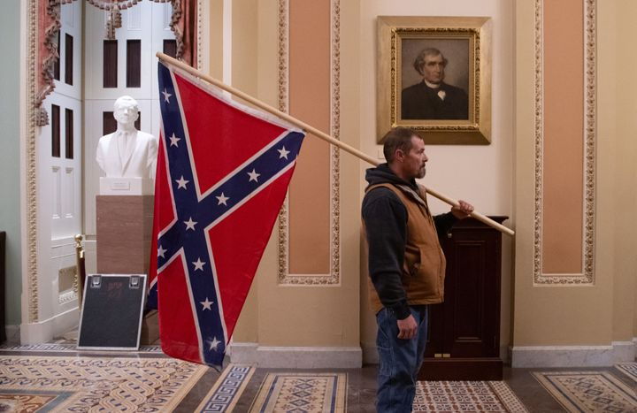 Kevin Seefried holds a Confederate flag outside the Senate on Jan. 6. He stormed the Capitol with his son, Hunter.