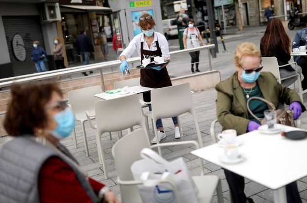 Una camarera con una mascarilla y guantes de protección trabajando en una