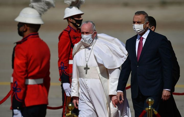 Pope Francis walks alongside Iraq's Prime Minister Mustafa al-Kadhem upon his arrival in Baghdad on March 5, 2021 on the firs