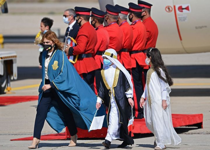 Iraqi children dressed in traditional outfits join a protocol member wearing a protective mask as they welcome Pope Francis a
