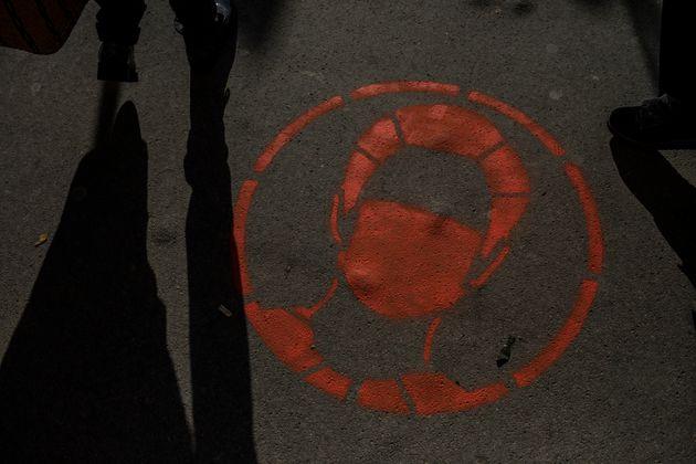 El dibujo de un hombre con mascarilla, en el suelo de una