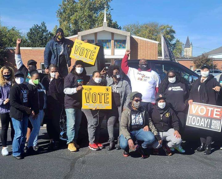 Savvy Shabazz (center, arm raised) is seen with members of the group All of Us or None Louisville during a voter registration