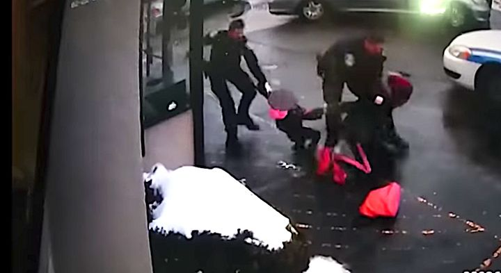 One officer can be seen tackling the woman while another tries to wrest away her 3-year-old daughter.