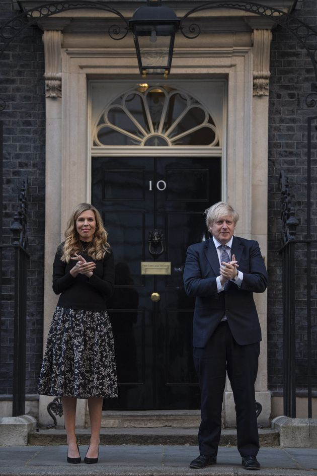 Boris Johnson and Carrie Symonds stand in Downing Street, London, to join in the applause to salute local heroes during the nationwide Clap for Carers to recognise and support NHS workers and carers fighting the coronavirus pandemic
