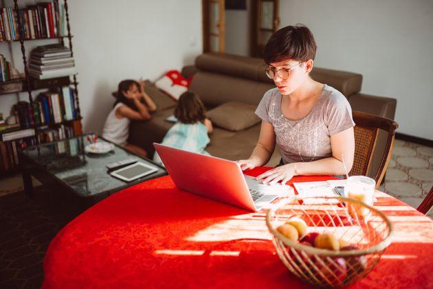 Una madre trabaja en la mesa del salón, con sus hijas jugando detrás en el