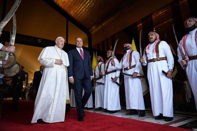 Iraq's Prime Minister Mustafa al-Kadhemi (R) welcomes Pope Francis at Baghdad International Airport's...