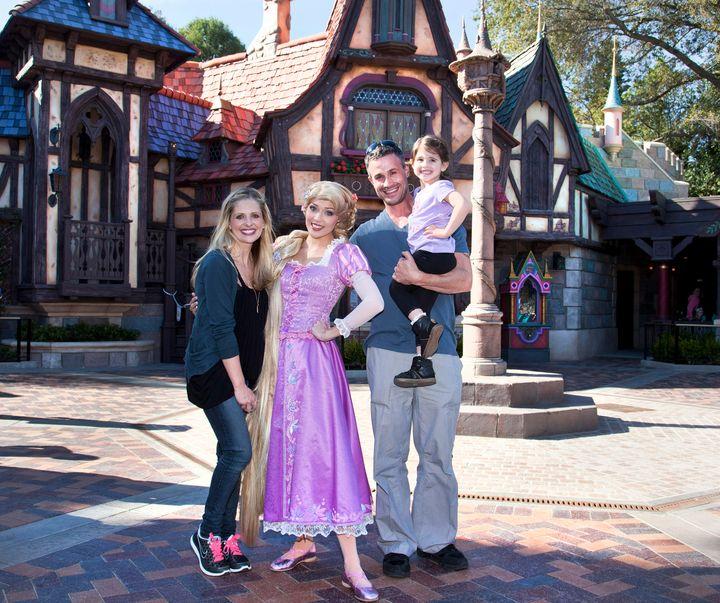 In this handout image provided by Disney Parks, Sarah Michelle Gellar, Freddie Prinze Jr. and their daughter Charlotte meet Rapunzel at Disneyland in 2013.