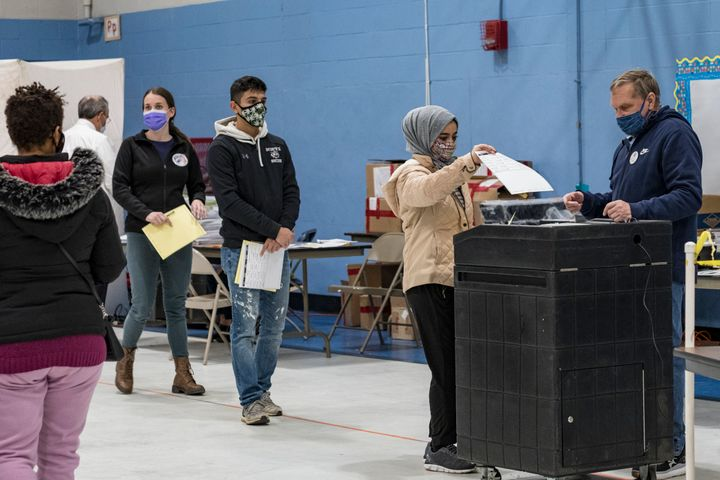 First-time voter Marwah Al Thuwayni, 18, casts a ballot at the Bishop Leo E. O'Neil Youth Center polling place in Manchester, New Hampshire, Nov. 3, 2020.