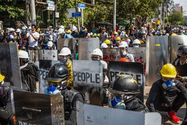 Anti-coup protesters protect themselves on Monday behind makeshift shields during a demonstration against...