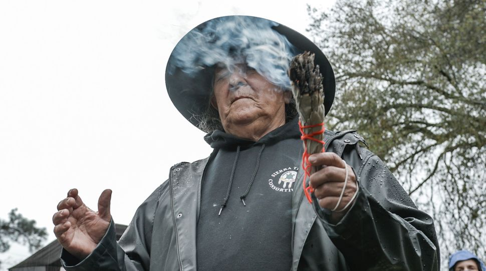 The tribe's spiritual leader, Keith Turner, begins burn day with a ceremony, blessing each member of the group with cle