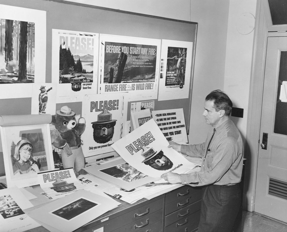A park ranger in an office with a plethora of posters about preventing forest fires, most of which feature Smokey the Bear.&n