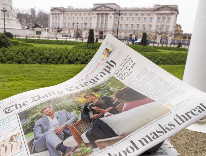 A British newspaper flutters in the wind outside Buckingham Palace in London the day after the Duke and Duchess of Sussex's i