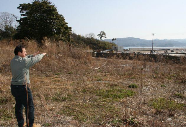 津波が来るまで経営した民宿「向」の跡地を案内する佐々木昌則さん(2015年撮影)