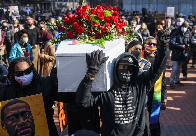 MINNEAPOLIS, MN - MARCH 7: People carry a casket covered in roses during a march in honor of George Floyd...