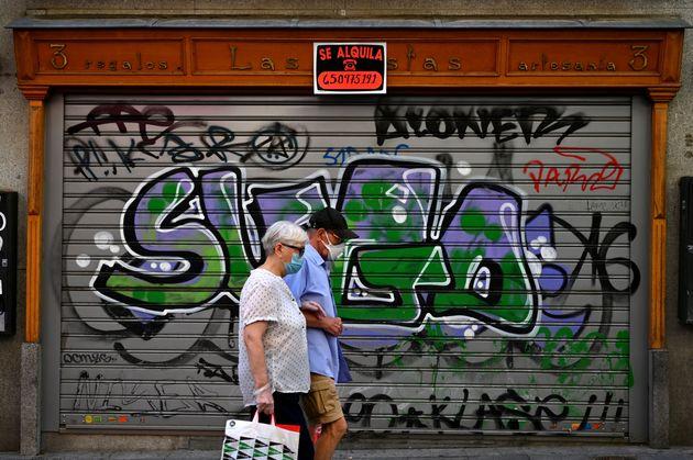 Una pareja pasea por delante de una tienda cerrada en