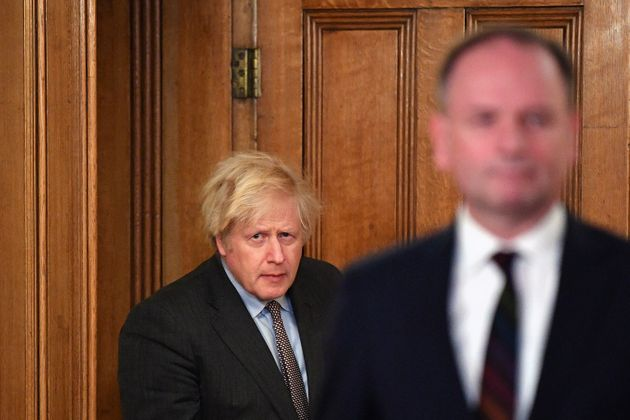 Boris Johnson arrives with Sir Simon Stevens, Chief Executive of the National Health Service, for a media...
