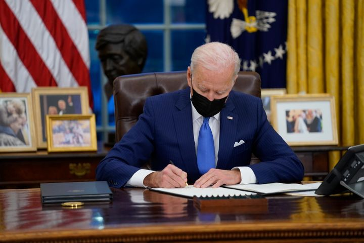 President Joe Biden signs an executive order on immigration in the Oval Office of the White House, Feb. 2, 2021.