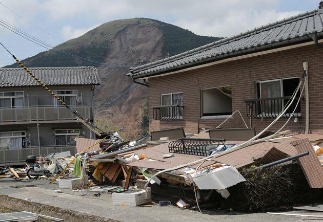 地震で倒壊した東海大阿蘇キャンパス周辺のアパートと土砂崩れした山=2016年4月22日、熊本県南阿蘇村