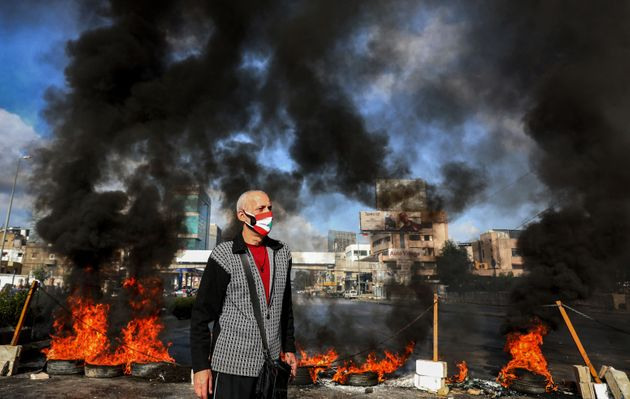 A man wearing a cross necklace and clad in mask depicting the Lebanese flag stands next to flaming tires...