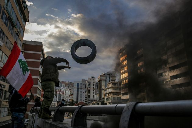 08 March 2021, Lebanon, Beirut: An anti-government activist throws a tire to block a highway during a...