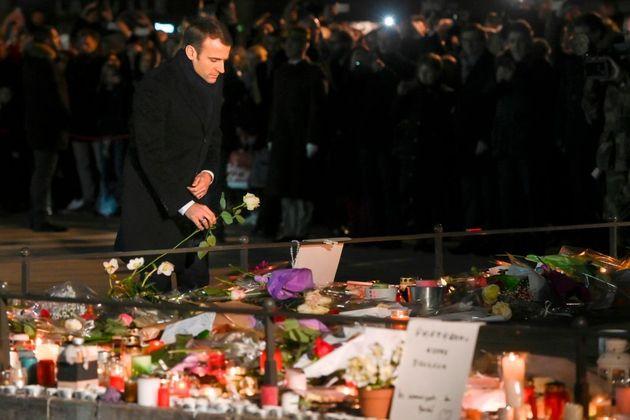 El presidente de Francia, Emmanuel Macron, coloca una rosa blanca en un monumento cerca del mercado navideño...