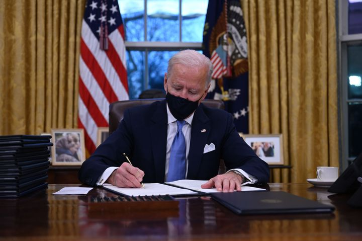 President Joe Biden signs a series of orders after being sworn in as president on Jan. 20, including one that rescinded Donal