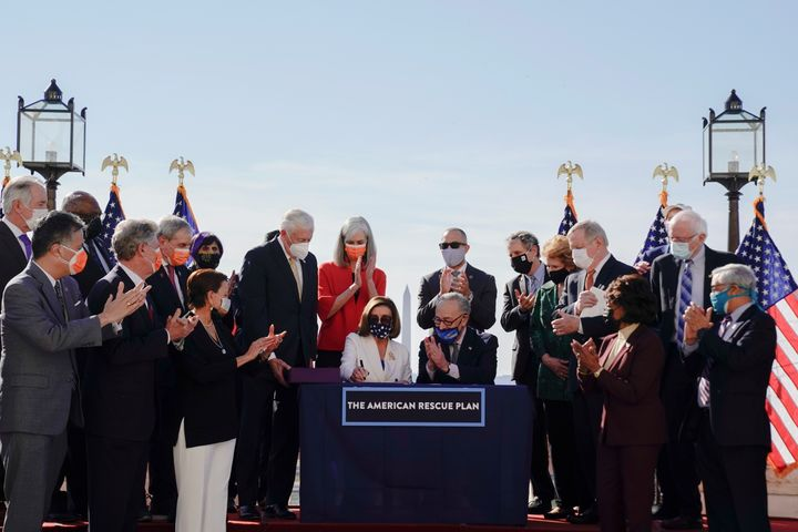 House Speaker Nancy Pelosi signs the American Rescue Plan as Senate Majority Leader Chuck Schumer and others applaud during t