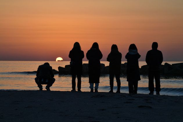 東日本大震災から10年となった2021年3月11日、宮城県荒浜地区の海岸で津波の犠牲者に祈る人たち