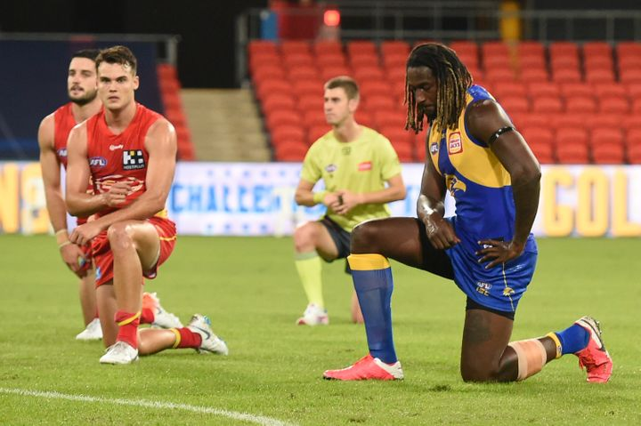 Nic Naitanui, right, of West Coast Eagles takes a knee in support of the Black Lives Matter movement before the Round 2 AFL match between the Gold Coast Suns and the West Coast Eagles at Metricon Stadium on June 13, 2020, in Gold Coast, Australia.