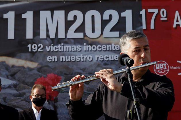 Un músico toca una melodía con una flauta travesera en la estación de Atocha durante el homenaje a las...