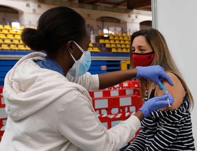 Una enfermera administra una vacuna de AstraZeneca a Paula en el polideportivo Germans Escalas, en