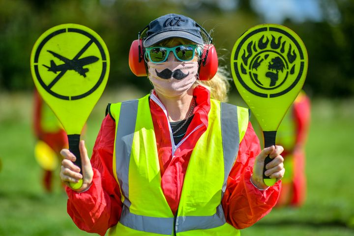 Activists from Extinction Rebellion, dressed as aircraft marshals, as they take part in a protest against the plan to expand Bristol International Airport in August, 2020.