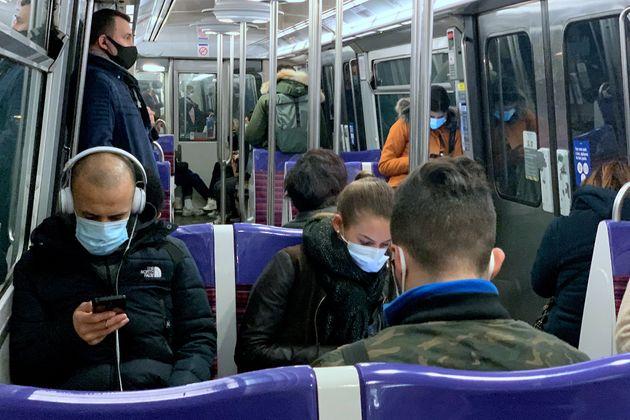 À Paris, des Français sur la ligne 13 du métro portent un masque pour lutter contre...