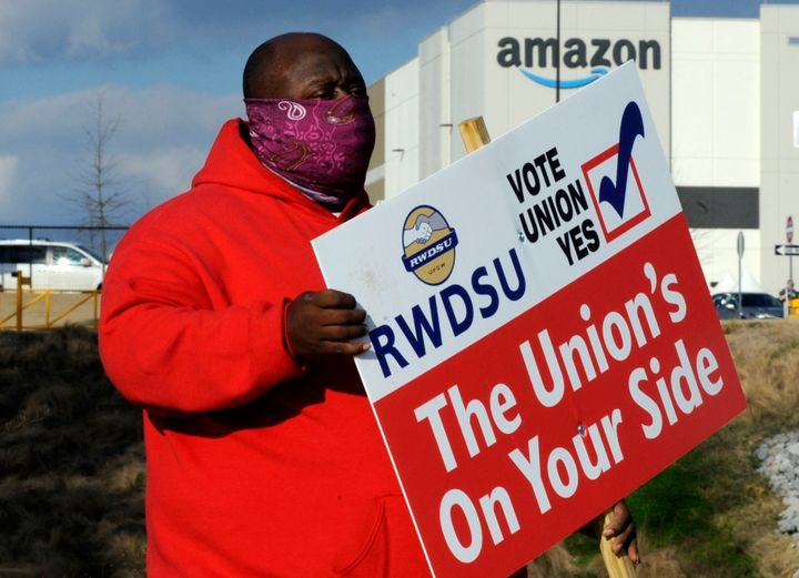 Michael Foster of the Retail, Wholesale and Department Store Union holds a sign outside an Amazon facility, Feb. 9.