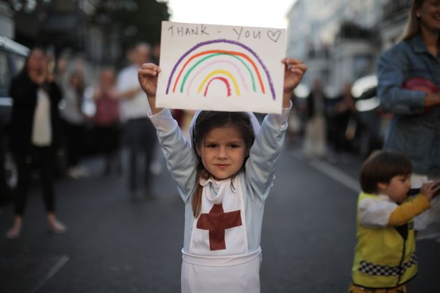 Maria Sole, 4, dressed in a small nurses outfit holds up a rainbow drawing with the words 'Thank