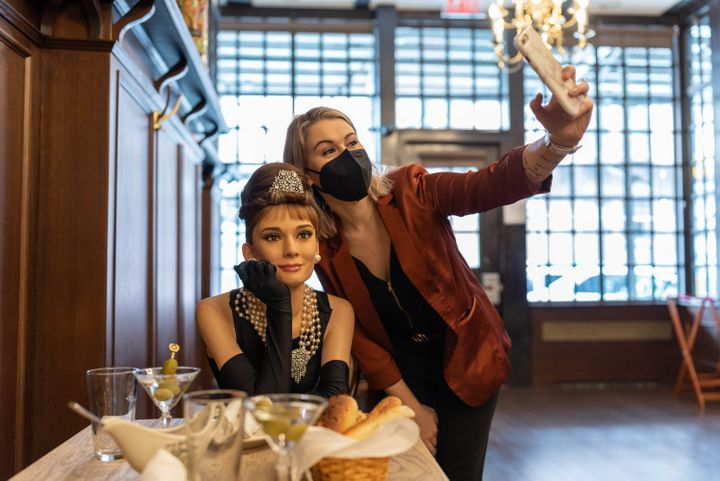 A patron snapping a photo with a wax figure of Audrey Hepborn at Peter Luger's Steakhouse in Brooklyn in March 2021.