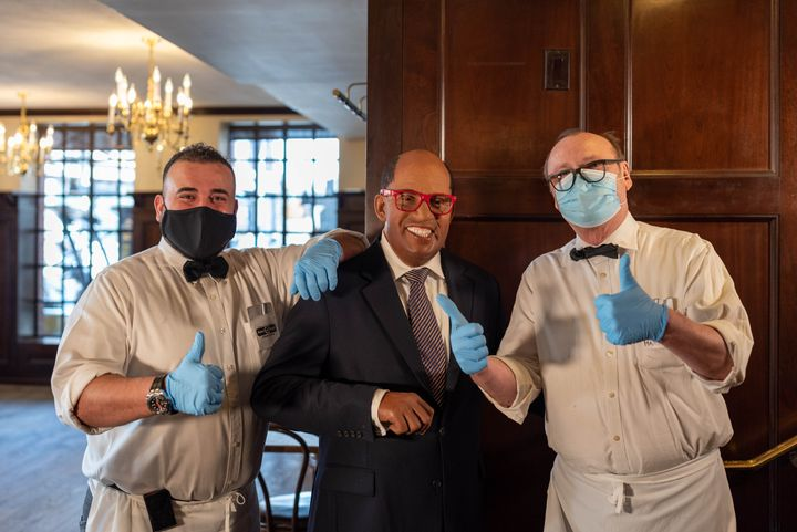 Two waiters get their photo taken with a wax figure of Al Roker at Peter Luger's Steakhouse in Brooklyn in New York City on M