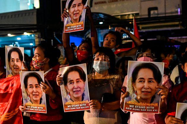 ミャンマー総選挙で、与党・国民民主連盟(NLD)を率いるアウン・サン・スー・チー氏のポスターを掲げる支持者たち=2020年11月9日、ミャンマー・ヤンゴン