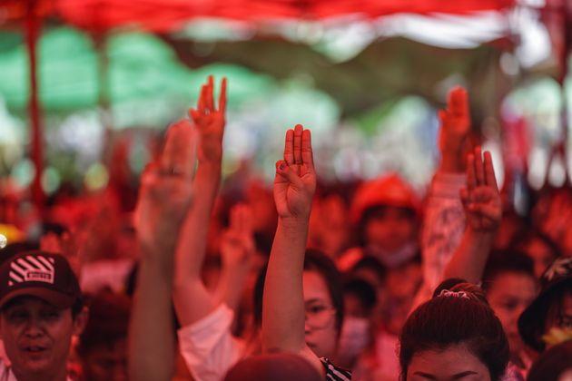 抗議のシンボルである3本の指を掲げて軍事クーデターや弾圧に抗議する人々=2021年3月13日、ヤンゴン