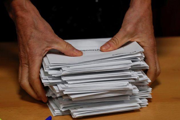 Un miembro de una mesa electoral procede al recuento de votos en un colegio electoral de Madrid, en