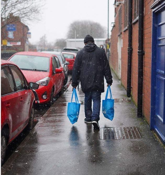 A man carrying food parcels to help those in
